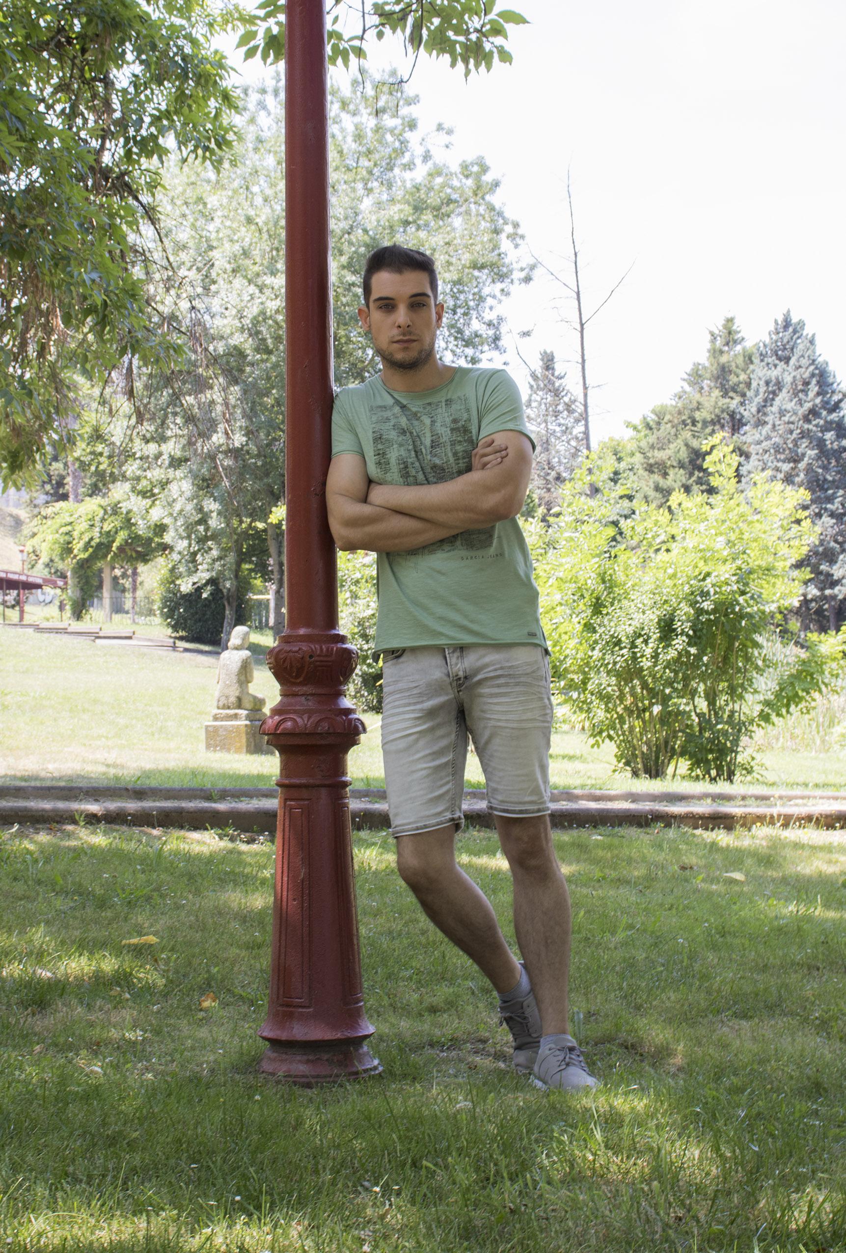 Outfit hombre: look de camiseta verde con dibujo en negro y pantalones cortos en gris lavado
